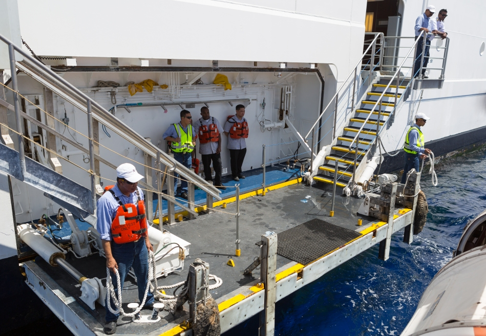 Crew members standing by to assist passengers with disembarking from the tender at the side of the ship.