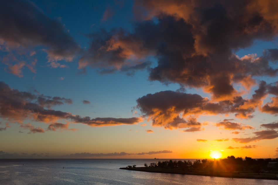 The last sunset from the balcony of our stateroom on the ship looking west across the harbour entrance in Honolulu.