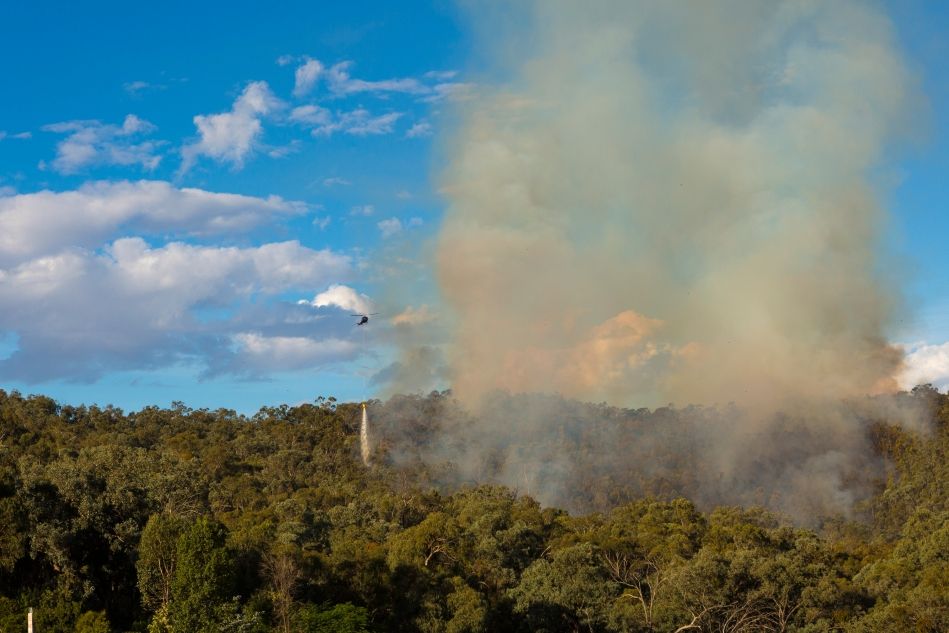 A helicopter dumping its' load on the leading edge of the fire.